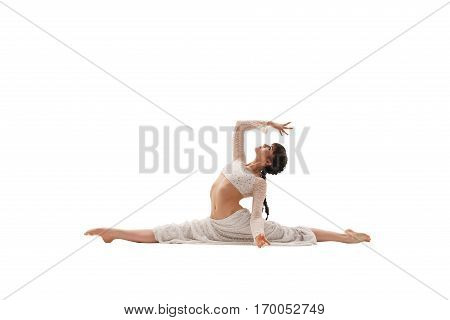 Young girl in white lace skirt and doing splits and streching gracefully in studio
