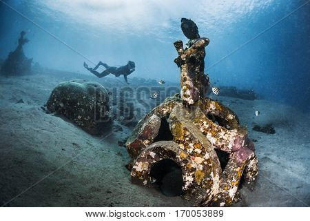 Free diver exploring the underwater statue in a tropical sea