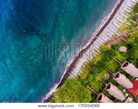 Aerial shot of Japanese ship wreck sunk near the coast. Traditional boats on the beach and green garden with bungalows on the land, Bali island, Indonesia