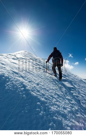 Mountaineer reaches the summit of a snowy peak. Concept: courage, perseverance, strength. Swiss Alps, Zermatt, Europe.