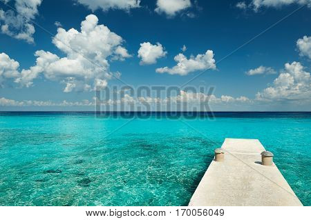 White dock in blue crystal water with deep clear sky. Tourism paradise water background
