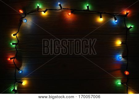 Christmas dark wooden background decorated with shining lights frame