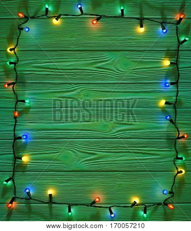 Christmas green color wooden rustic decorated  background  with shining lights, frame with copy space for your  text