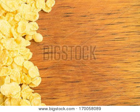 Dry Cornflakes for Breakfast Over Rustic Wooden Background with Copy Space. Healthy Cereal Vegetarian or Vegan Food