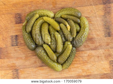 Homemade Pickled Gherkins or Cucumbers in the Shape of Heart on Wood Cutting Board