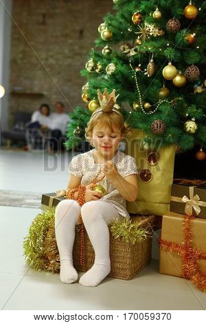 Happy girl princess at cosy home in front of the Christmas tree with family in background.