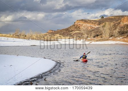 winter kayaking in Colorado - senior male paddler in a red whitewater kayak on  Horsetooth Reservoir near Fort Collins