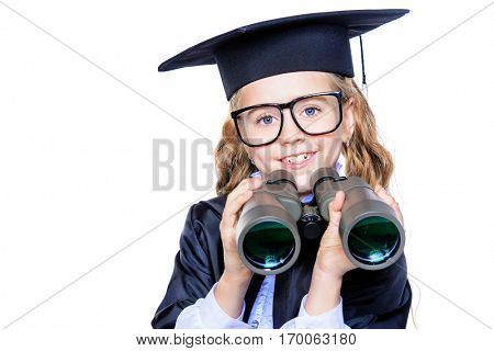 Smart schoolgirl  in academic hat and a gown looking through binoculars. Educational concept. Isolated over white. Copy space.