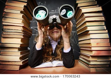 Portrait of a smart schoolgirl  looking through binoculars. Books and school blackboard. Educational concept.