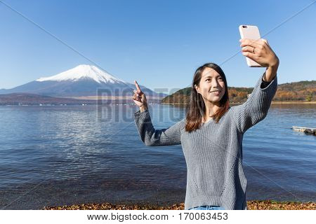 Woman take photo by cellphone in  lake yamanaka with Fujisan