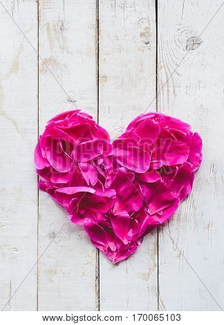 top view of red peonies petals in heart shape as love symbol for wedding or valentines day decorate on white wooden texture board background