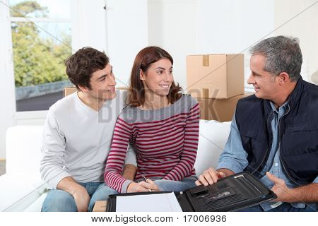 Young couple signing contract for home moving