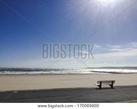 Solitary bench overlooking Sandbanks beach in UK on a sunny blue sky day.