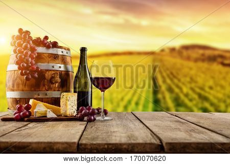 Red wine served on wooden planks with keg, vineyard on background, copyspace for text