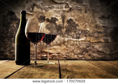 Small and old wine cellar with two glasses and bottle of red wine, served on wooden planks