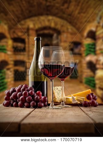 Small and old wine cellar with two glasses and bottle of red wine, served with grapes and cheese on wooden planks