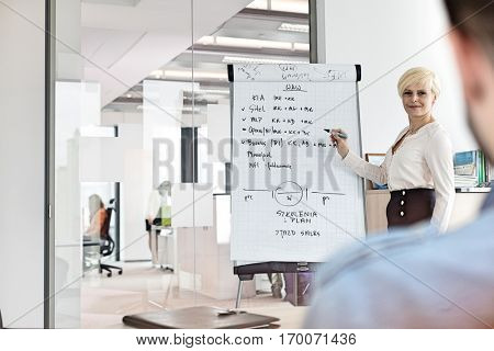 Mature businesswoman giving presentation using flipchart in board room