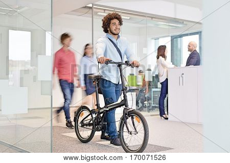 Young businessman walking with bicycle while colleagues in background at office