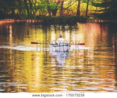 an old man rowing an aluminum boat while trolling for fish in a small pond toned with a retro vintage instagram filter effect action or app