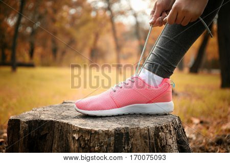 Woman tying up jogging shoes on snag