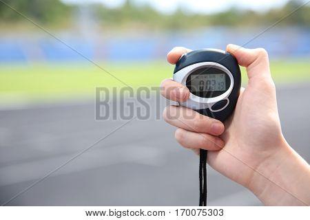 Female hand holding digital stopwatch, close up