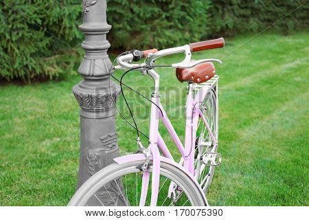 Bicycle parked near street lantern on green lawn, close up view