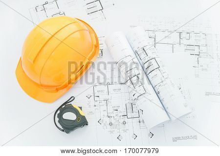 architects workplace - architectural blueprints with measuring tape safety helmet and tools on table. top view
