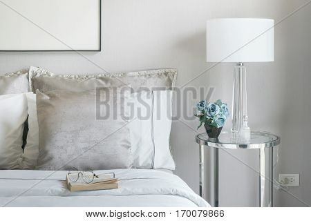 Light Gray And White Pillows On Bed With Flower Jar On Bedside Table