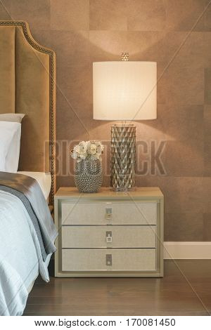 Luxury Style Reading Lamp And Flower Jar Setting On Beautiful Bedside Table Next To Bed