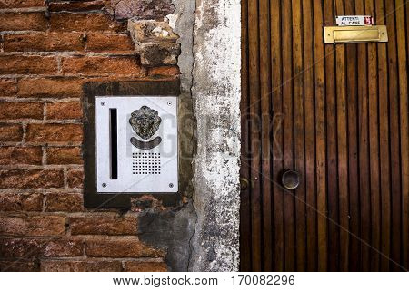 "brass doorplate and doorbell in a shape of a lion's head on an old, cracked brick wall and wooden door with a plate ""vicious dog"" in italian , Venice, Italy poster"