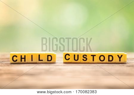 Text CHILD CUSTODY made of yellow blocks on wooden table against blurred background, closeup