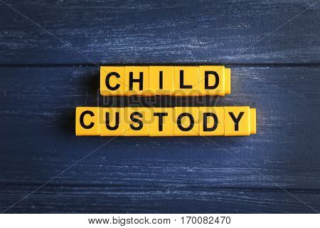 Text CHILD CUSTODY made of yellow blocks on wooden background, closeup