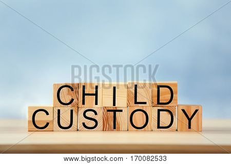 Text CHILD CUSTODY made of wooden blocks on table against blurred background, closeup