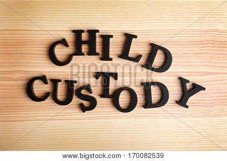Text CHILD CUSTODY made of black letters on wooden background