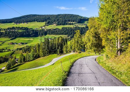 The forested mountains surrounded by green Alpine meadows. The road descends into the Val de Funes. Autumn in the Dolomites. The concept of ecological tourism