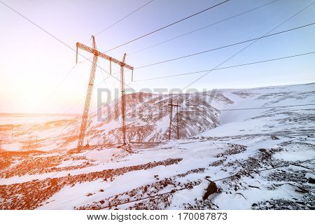 Support of the high-voltage power line. Winter mountain landscape.
