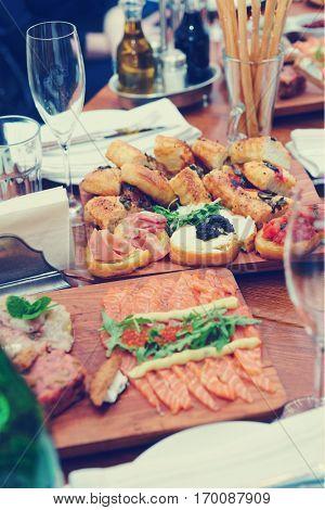 Restaurant table full of Italian starters, toned image