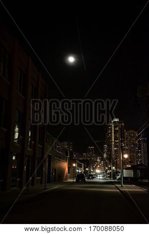 Dark Urban City Street at Night with Moon