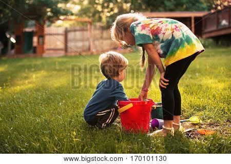 Young boy and girl on playground. back view. on grass
