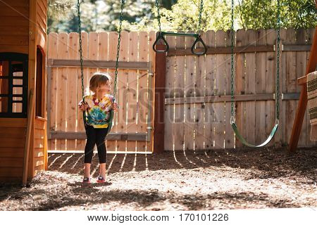 Girl on swing. front view. girl looking away. fence on background