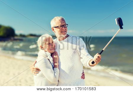 family, age, travel, technology and people concept - happy senior couple with smartphone selfie stick photographing and hugging on summer beach