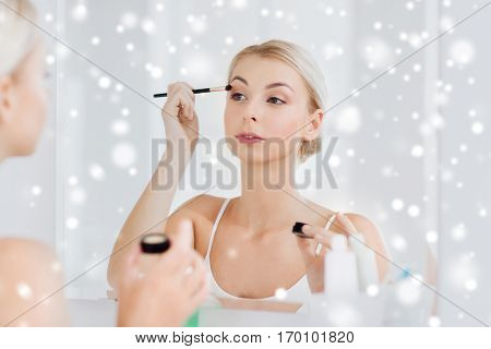 beauty, make up, cosmetics, morning and people concept - young woman applying eyeshade with makeup brush and looking to mirror at home bathroom over snow