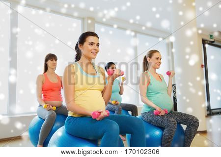pregnancy, sport, fitness, people and healthy lifestyle concept - group of happy pregnant women with dumbbells exercising on stability balls in gym over snow