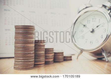 Concept business finance investment save money. Coins stack on wood table with calendar and alarm clock