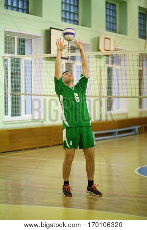 Middle age man in green sport wear trains with volleyball ball in gym