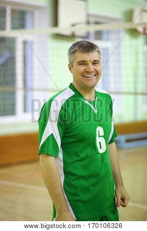 Middle age man in green sport wear stands in gym with net and smiles