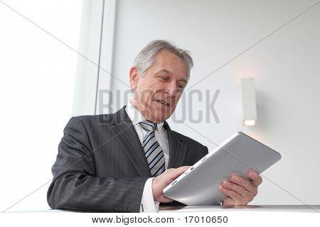 Senior man using electronic tab in building hall