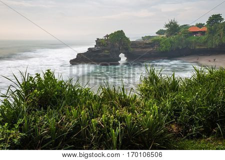 Temple of Tanah Lot with green plant on the foreground, Bali, Indonesia