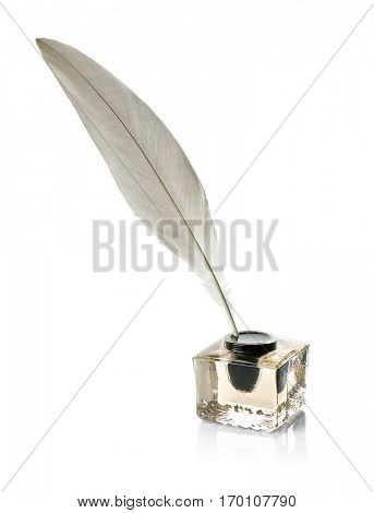 Feather pen in glass inkwell isolated on white