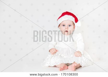 Cute baby sitting wearing cute Santa hat and white dress. Starry wallpaper background
